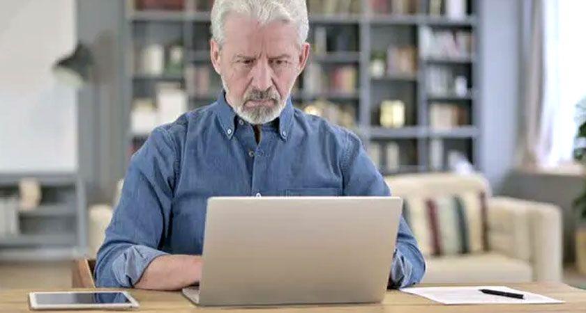 hombre mayor trabajando en su computadora